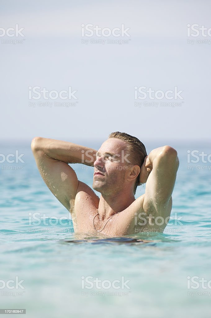 Man Stands in Sea Soaking up Sun Arms Behind Head royalty-free stock photo