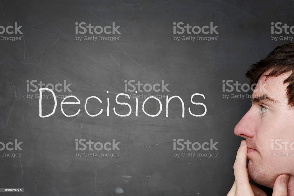 A man stands looking at chalkboard with DECISIONS on it. royalty-free stock photo