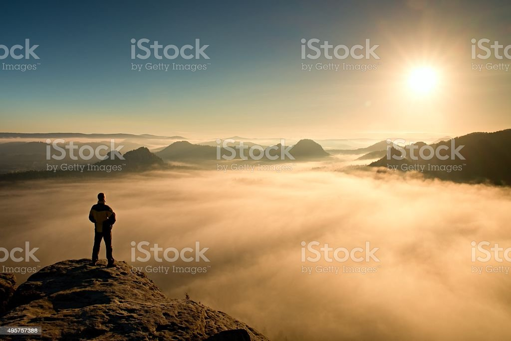 Man stands on peak and watching to Sun. Beautiful miracle stock photo