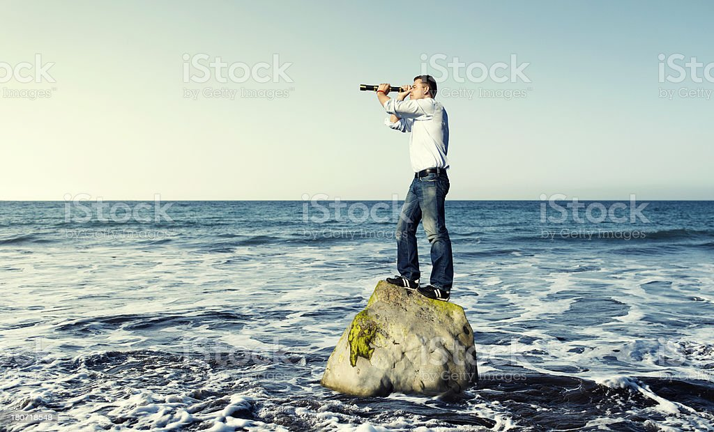 Man stands on rock in the sea with telescope stock photo