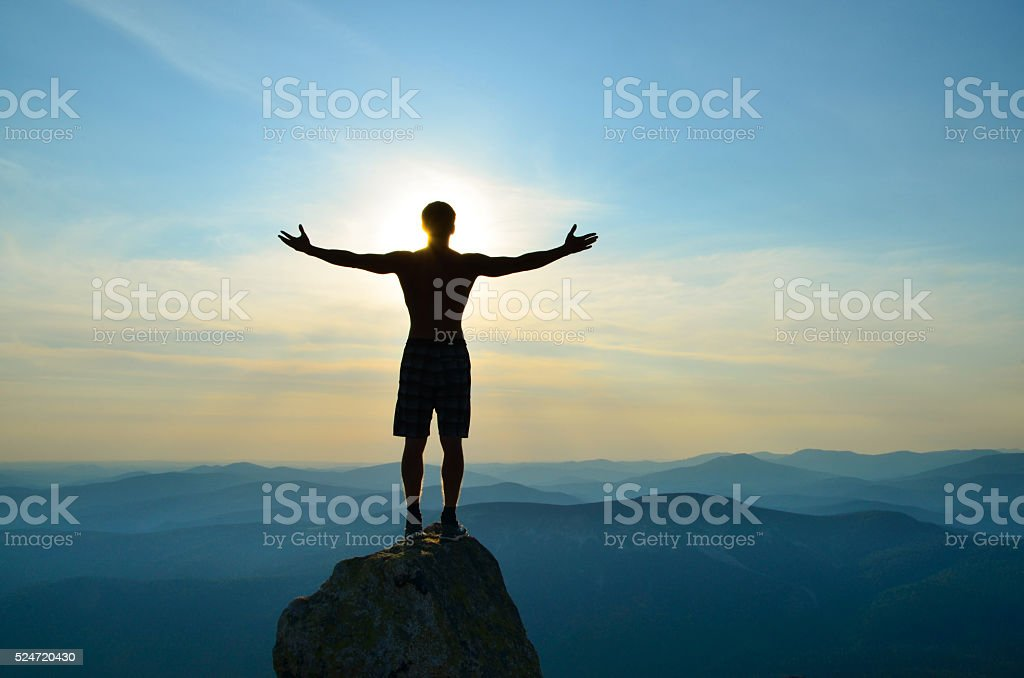 man stands on top of a mountain with open hands stock photo