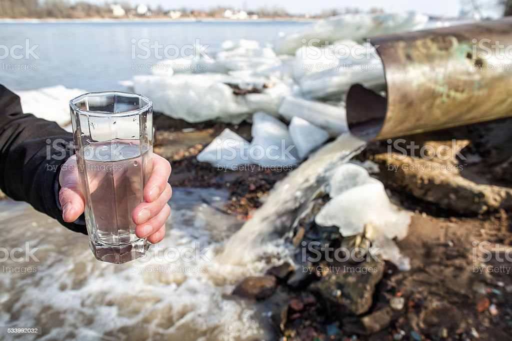 man stands with a glass filled with water from sewer stock photo