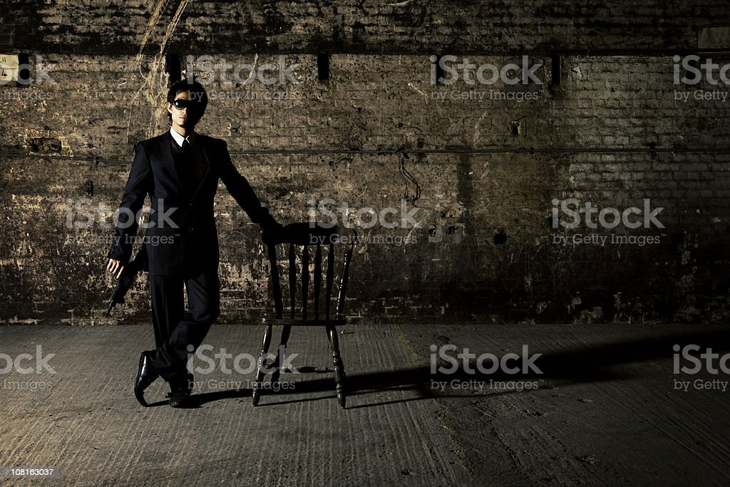 Man stands with gun in interrogation royalty-free stock photo
