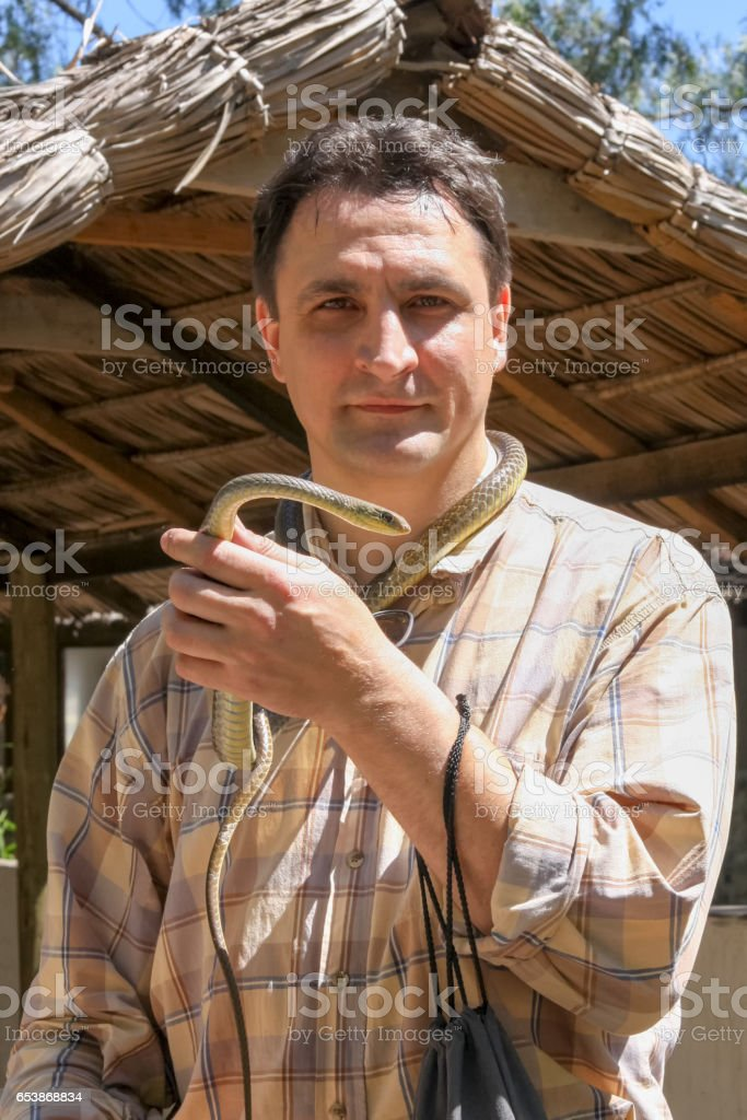 Man stands with snake tied like cravat on his neck stock photo