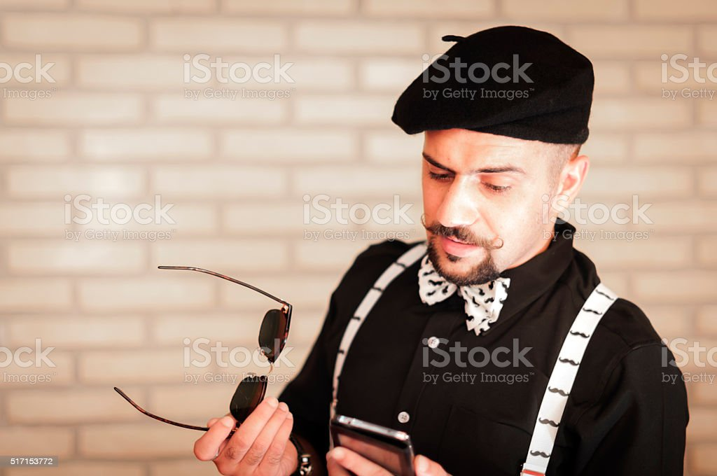 Man stares at the smartphone in confusion stock photo