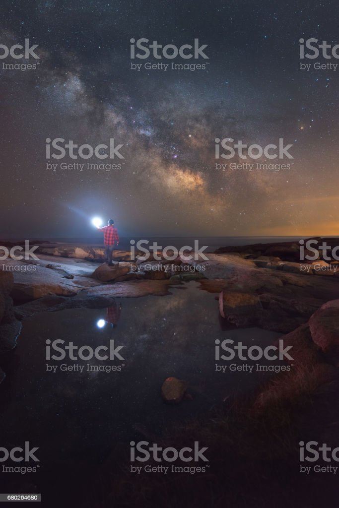 Man stargazing near a tide pool in Maine stock photo