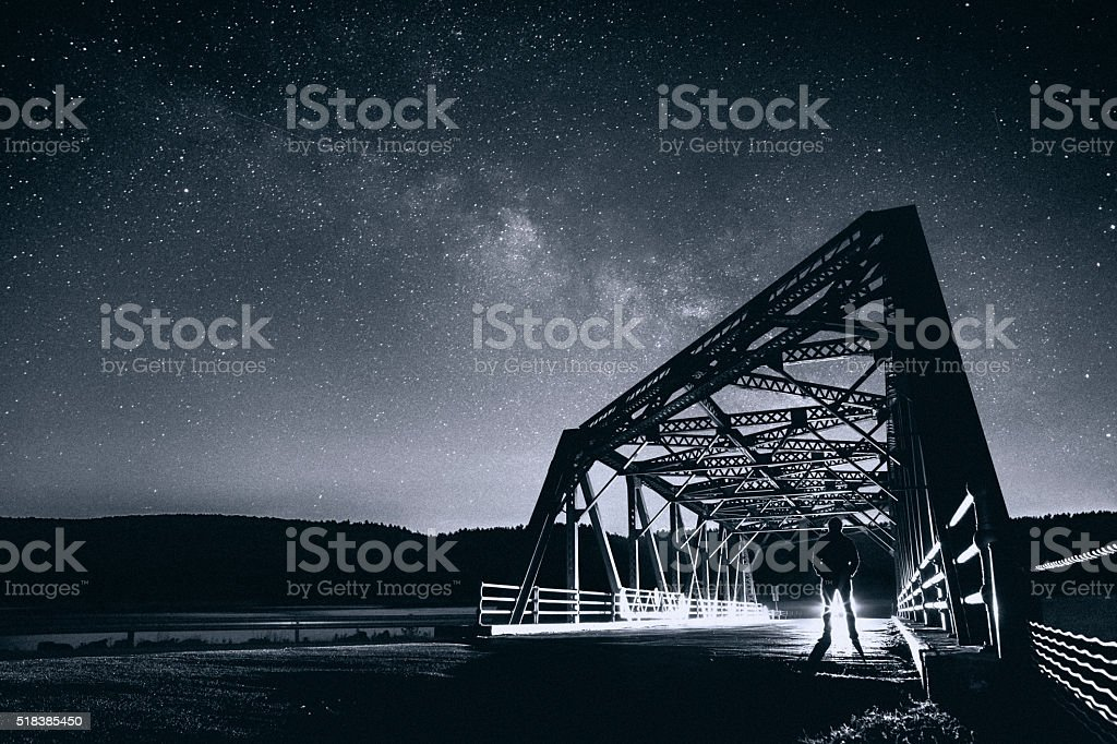 Man stargazing on the bridge stock photo