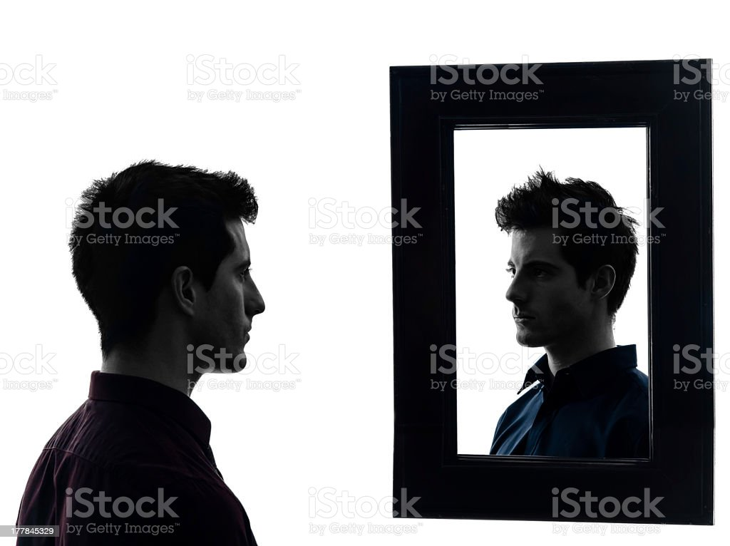 Man staring at his own reflection in mirror stock photo
