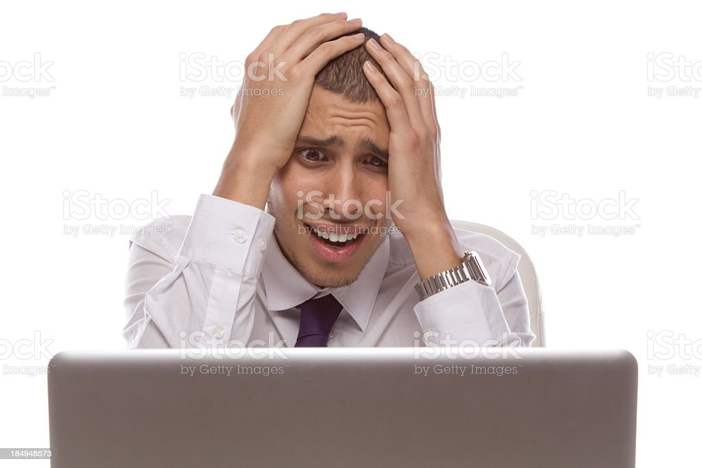 Man staring at laptop with shocked and desperate expression stock photo