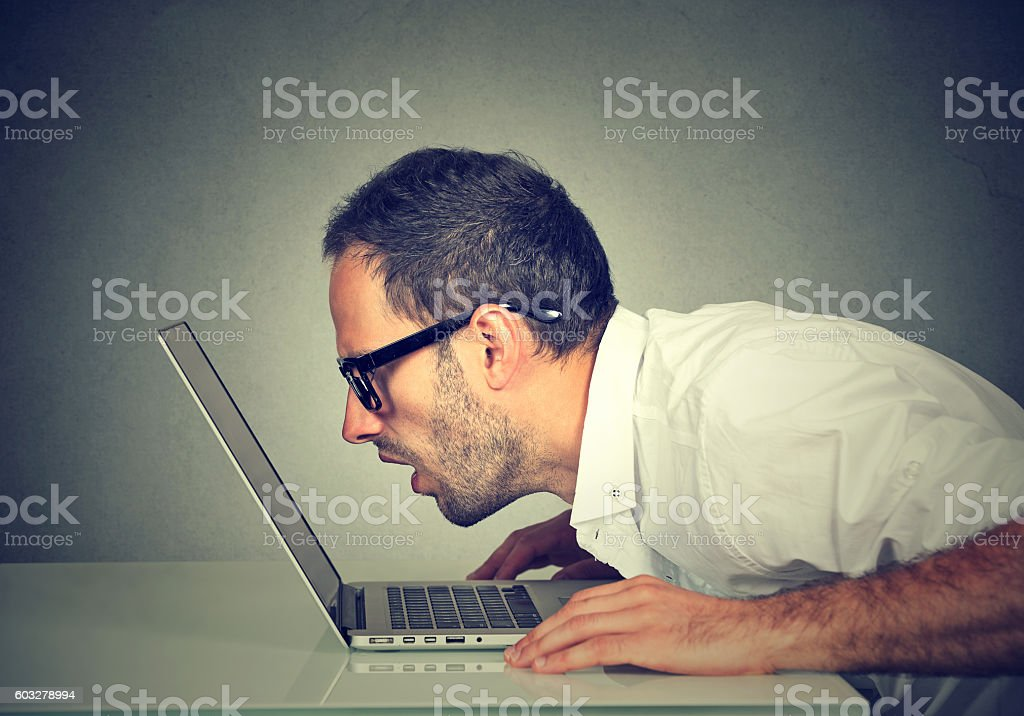 man staring closely intensely at laptop screen stock photo