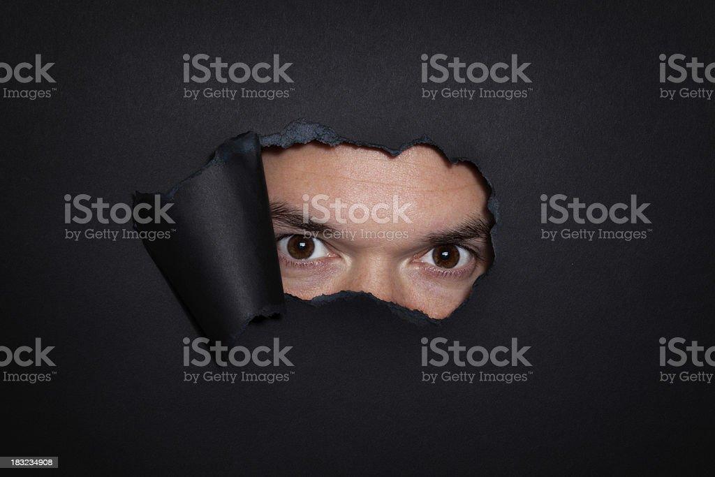 Man Staring Through Hole stock photo