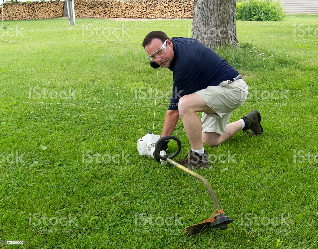 Man Starting A String Trimmer stock photo