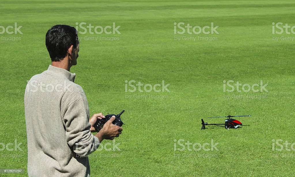 Man starting to fly a remote control helicopter stock photo