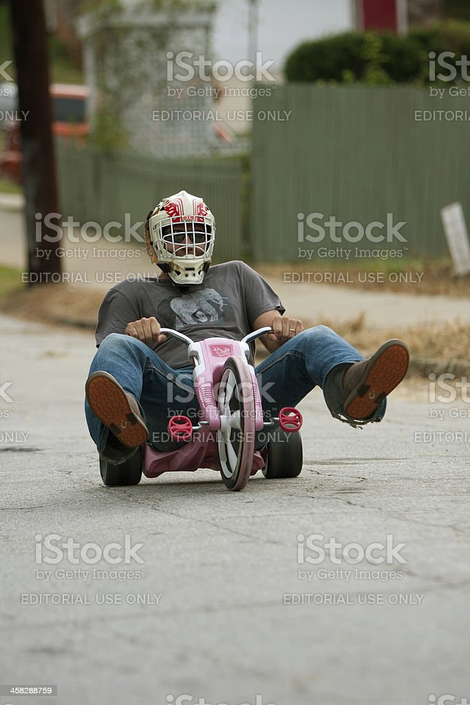 Man Steers Big Wheel Down Hilly Street royalty-free stock photo
