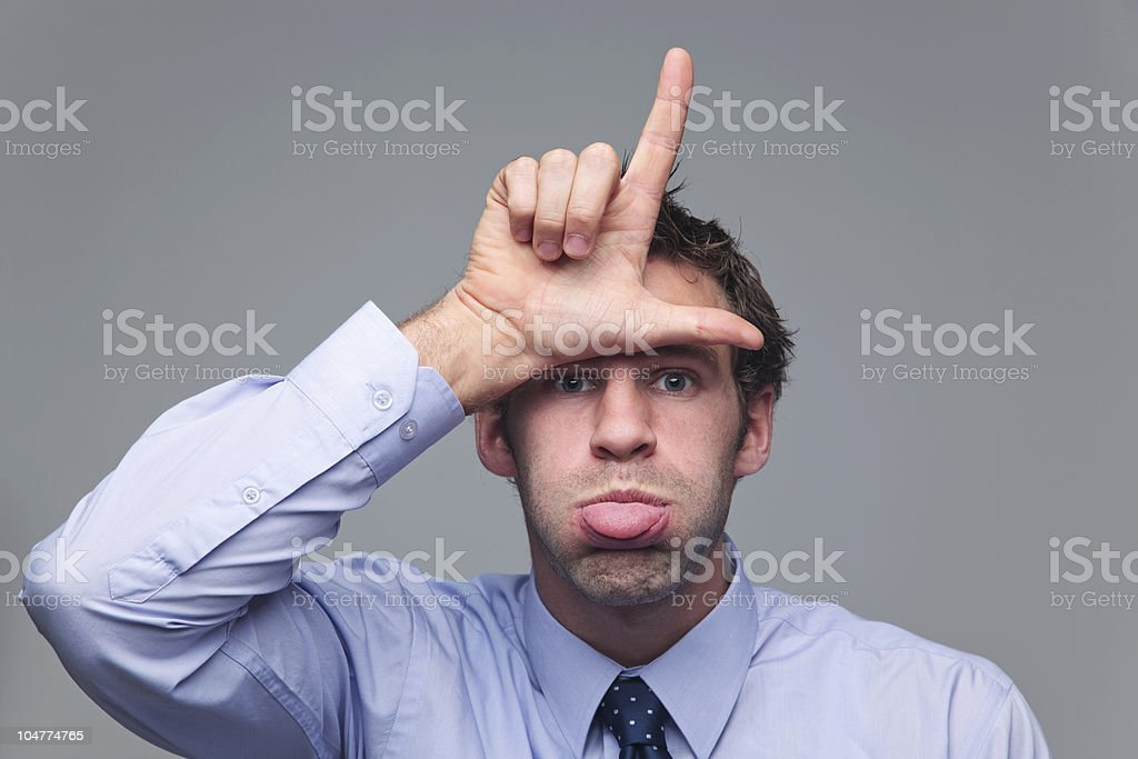 Man sticking his tongue out and gesturing loser stock photo