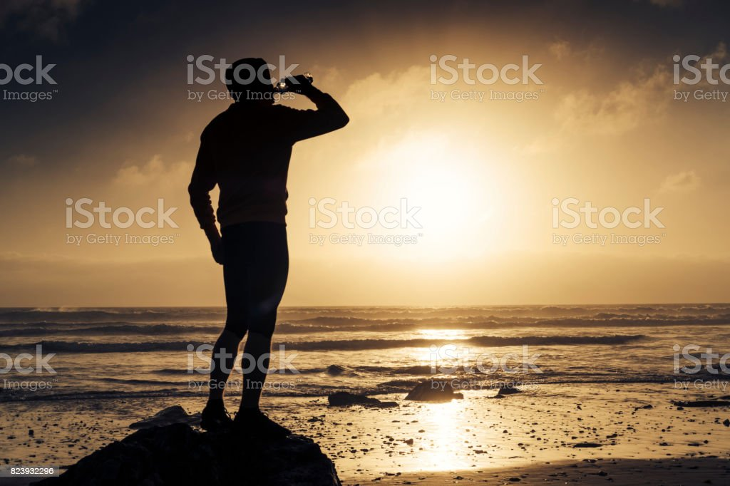 Man stood drinking water after a run along the beach. stock photo