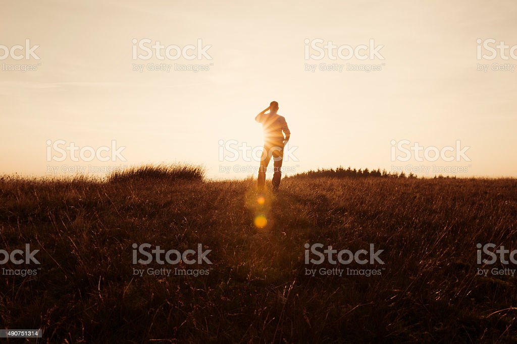Man Stood in the countryside looking at the sunset stock photo