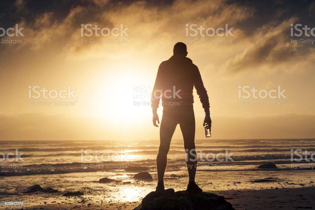 Man stood on a Beach near sunset after a run along the beach. stock photo