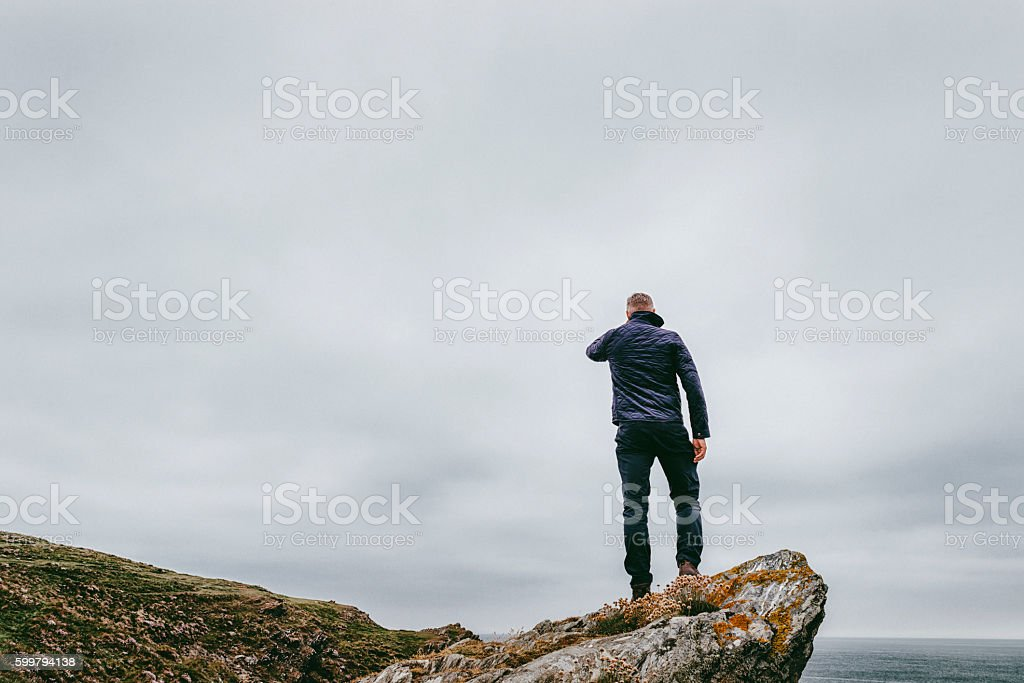 Man stood on a cliff top, grey dramtic foreboding sky stock photo
