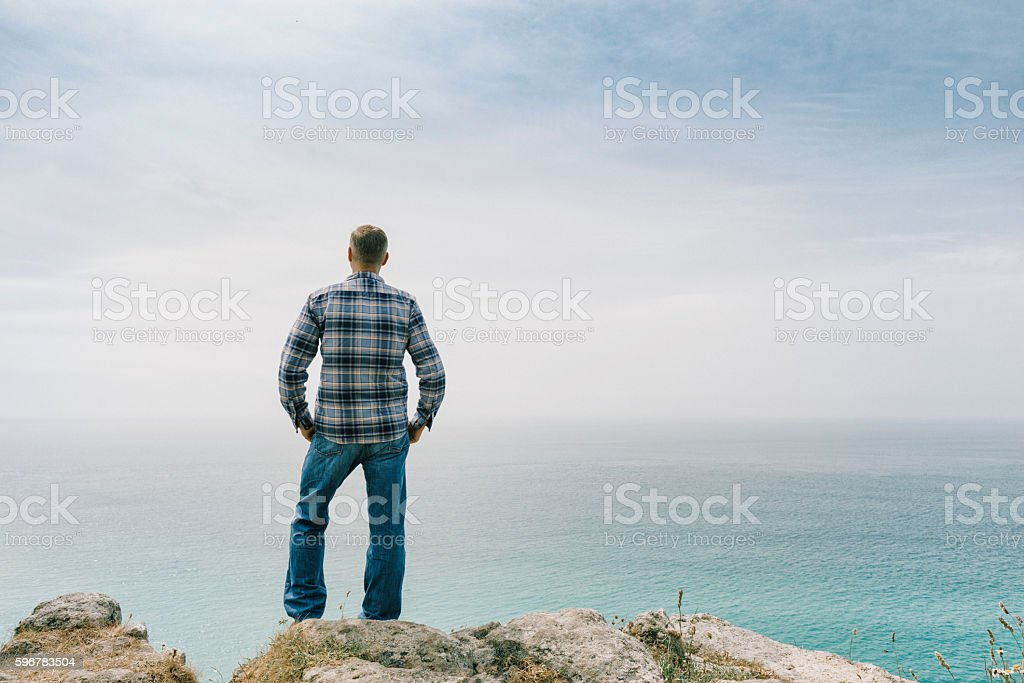 Man stood on Cliffs looking out over South Cornish Coast. stock photo