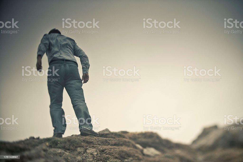 Man Stood ontop of a stormy clifftop stock photo