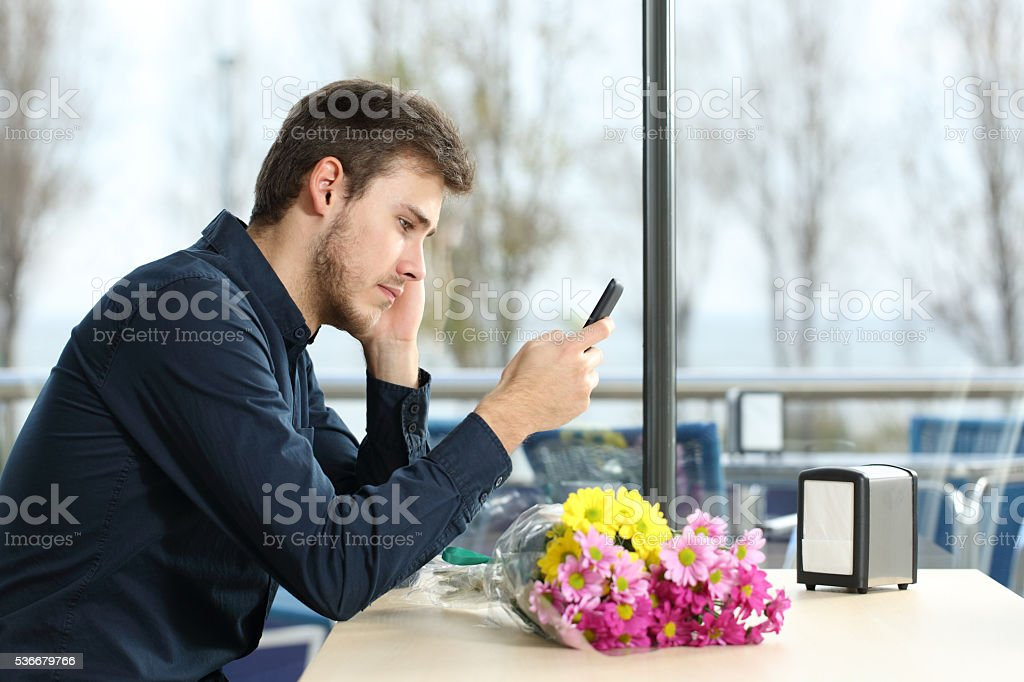 Man stood up in a date checking phone messages stock photo