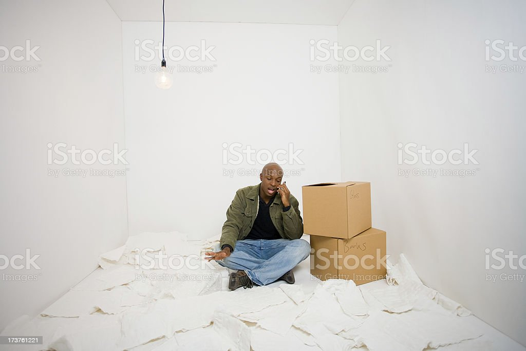 Man stops packing to sit and chat on cell phone royalty-free stock photo