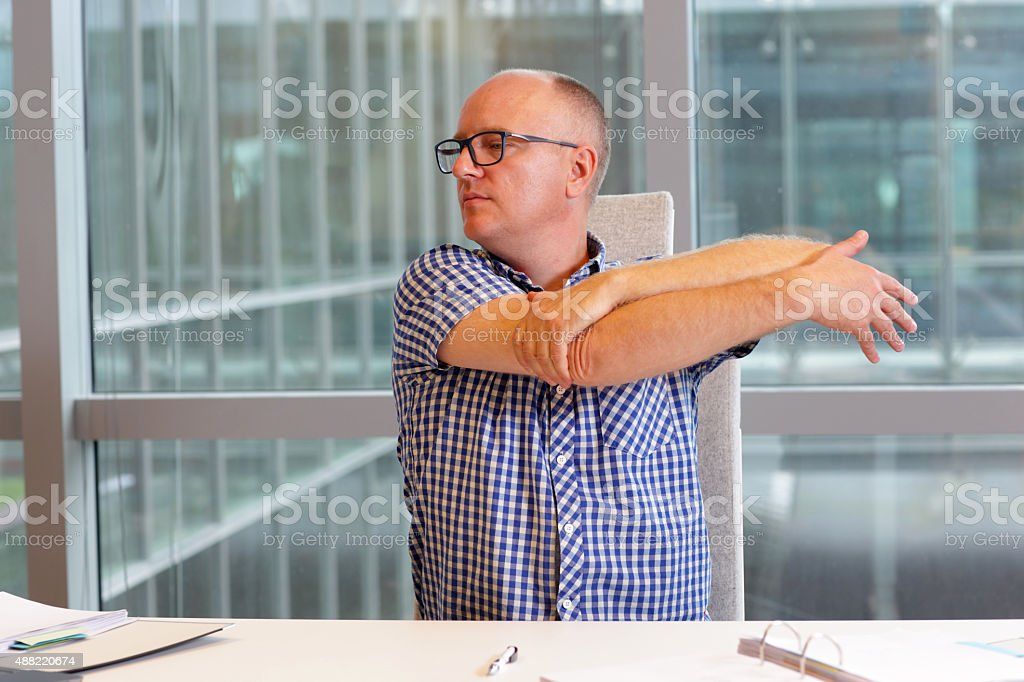 man stretching arm in his office stock photo