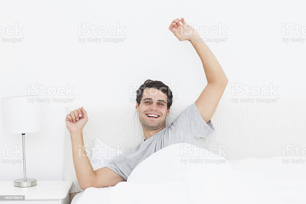 Man stretching arms in bed stock photo