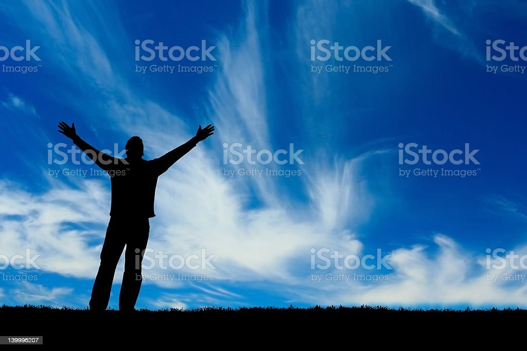 A man stretching his arms in faith stock photo