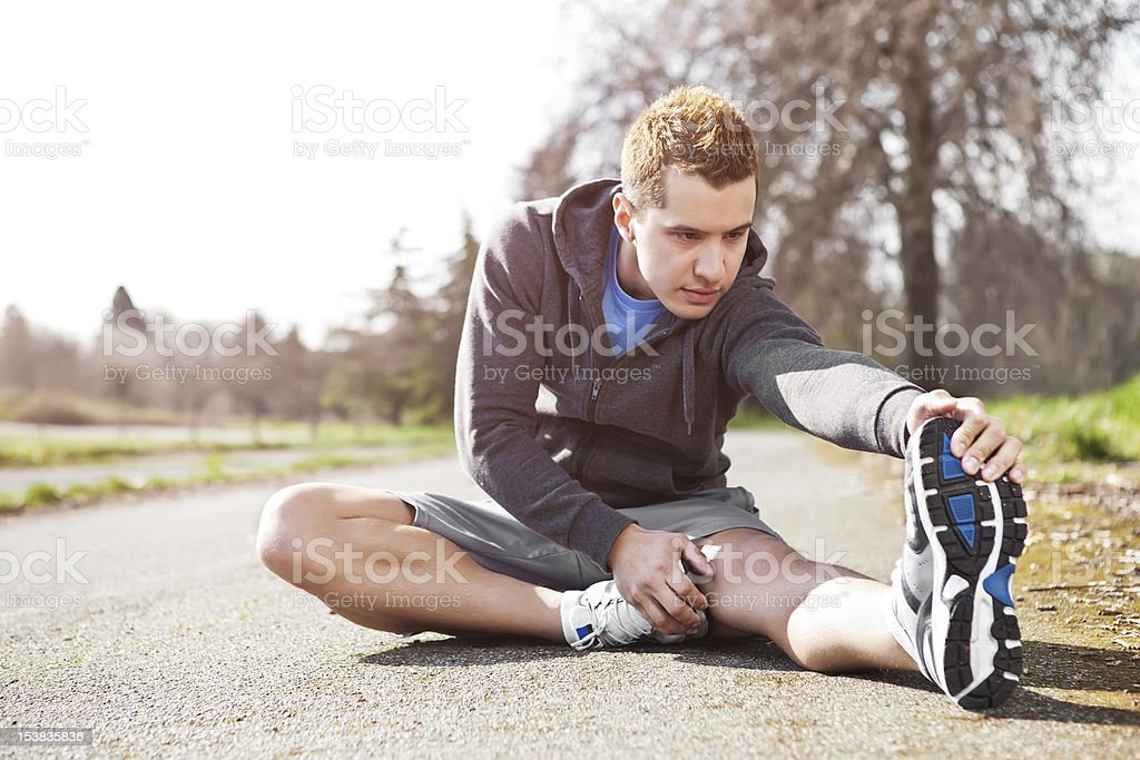 Man stretching his legs on the ground before a workout  royalty-free stock photo