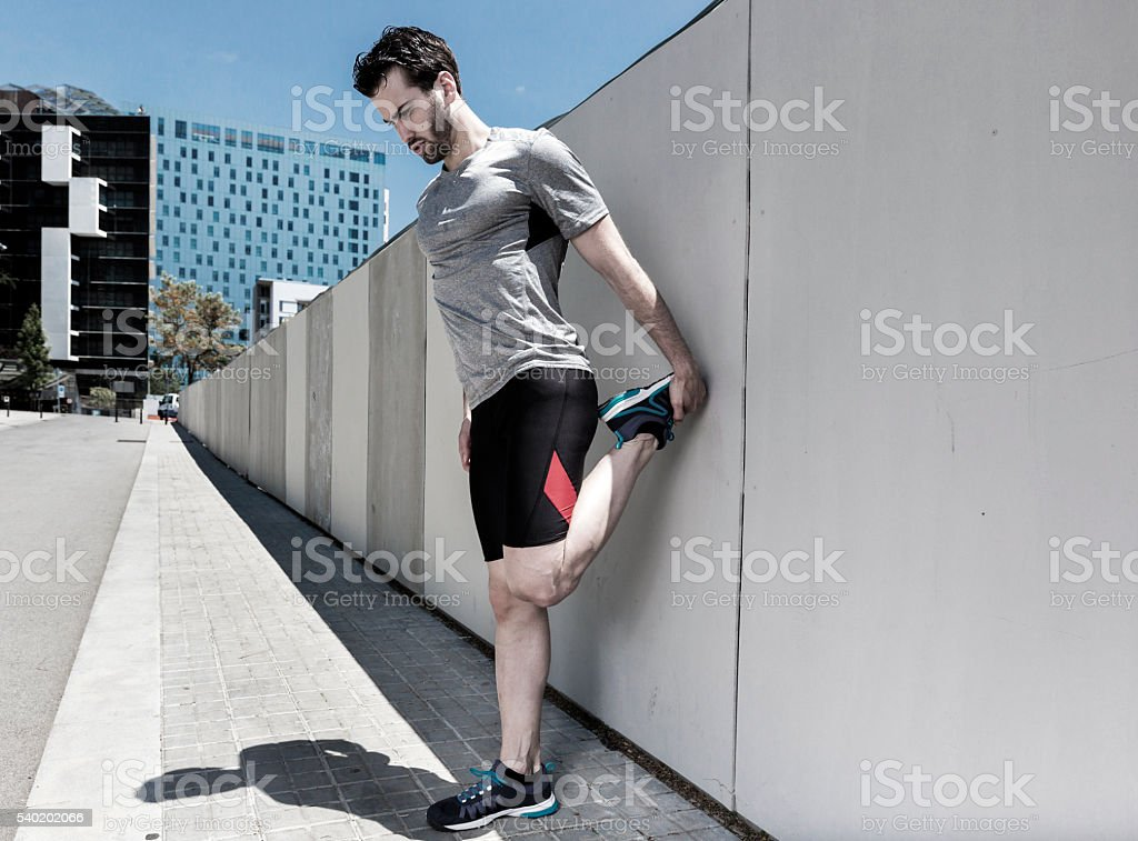 Man stretching in the city stock photo