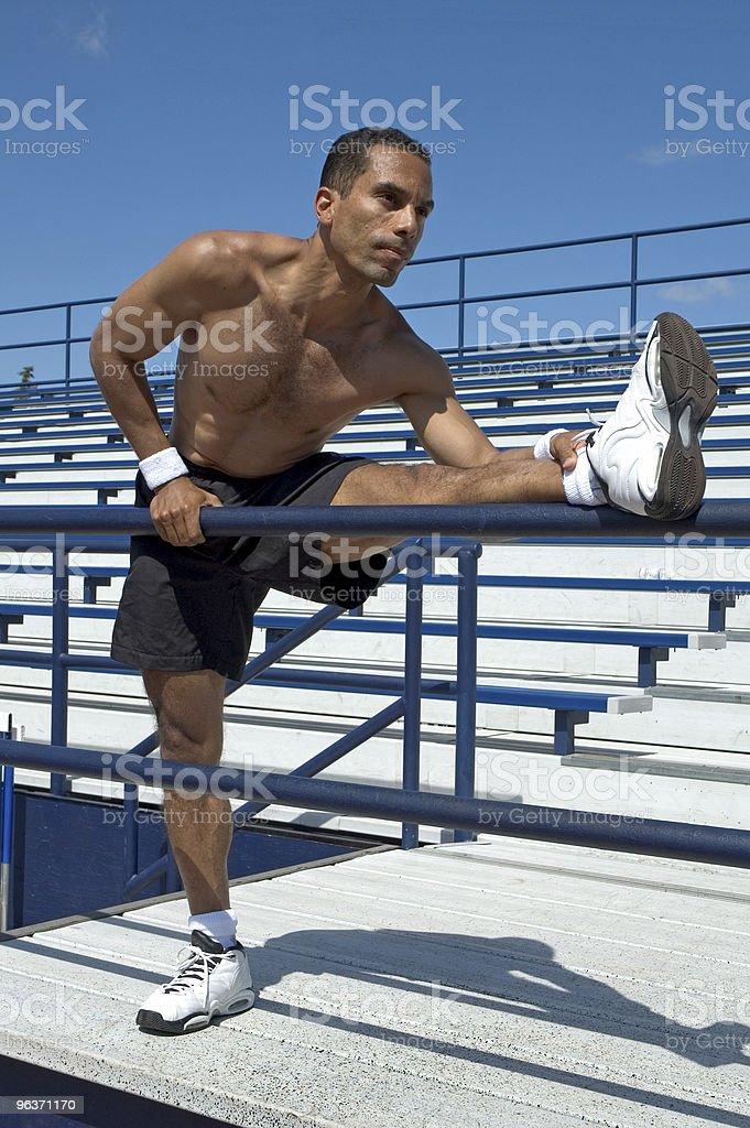 Uomo lo Stretching in tribuna foto stock royalty-free