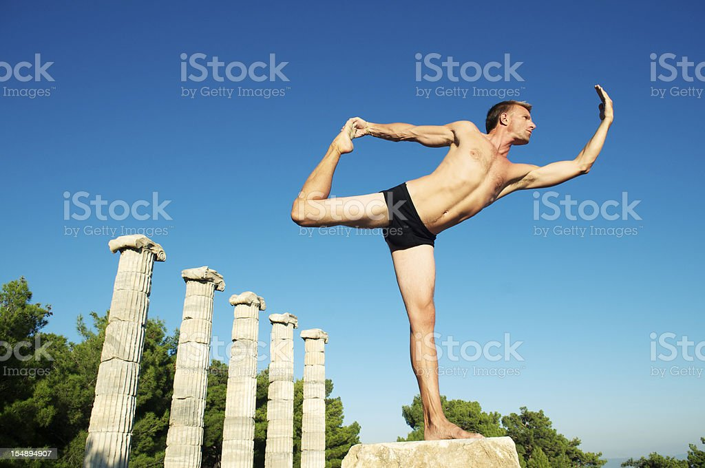 Man Strikes Classical Pose by Ancient Greek Columns royalty-free stock photo