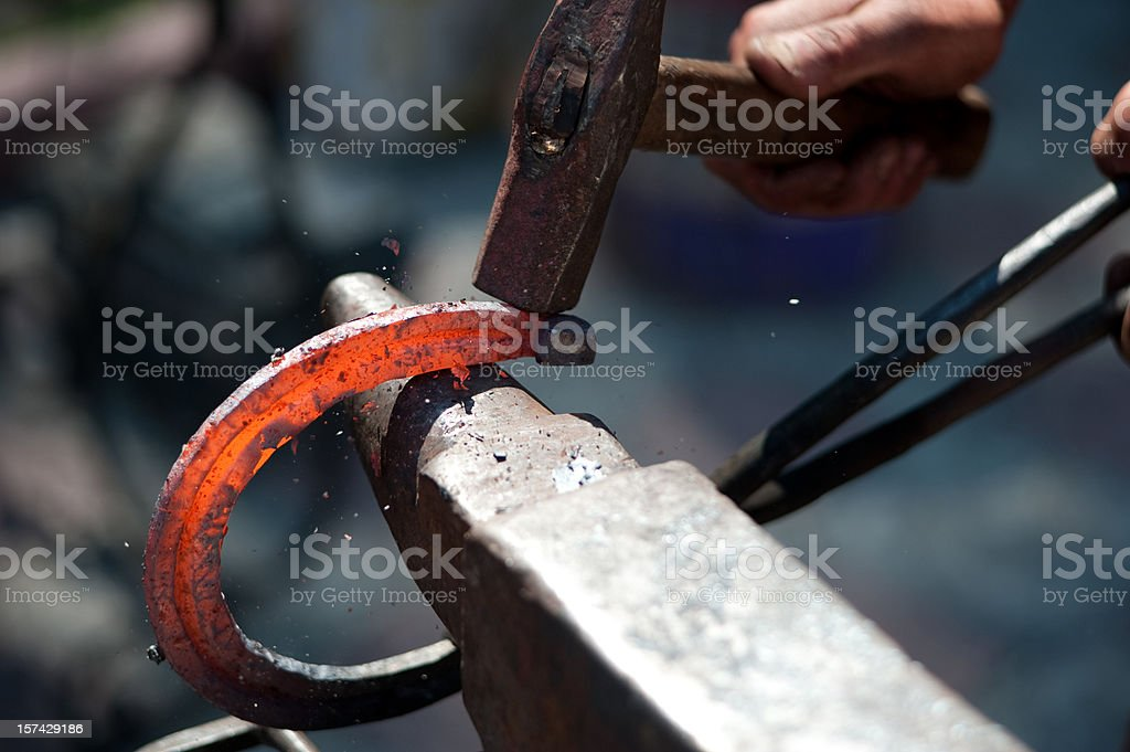 A man striking a red hot horseshoe on the anvil stock photo