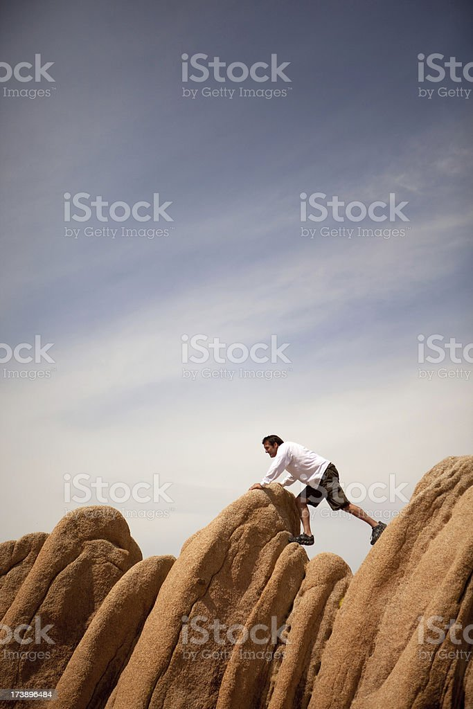 Man struggling to get over boulders in desert royalty-free stock photo