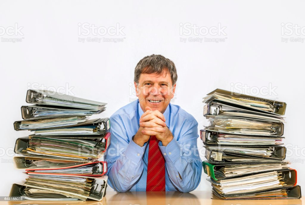 man studies folder with files at his desk stock photo