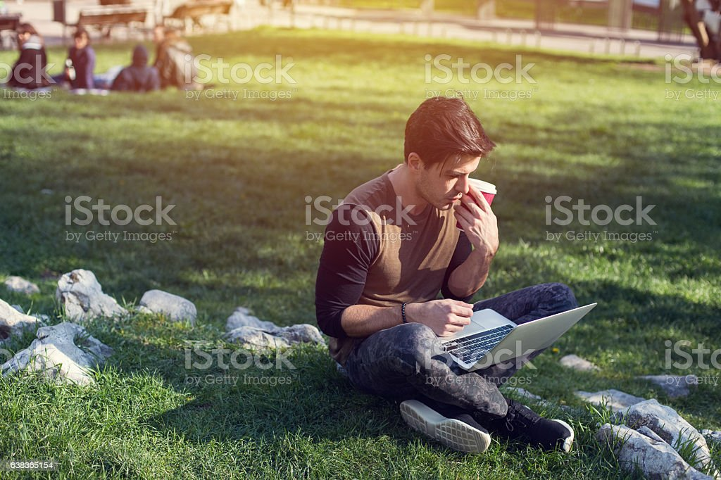 Man studying in the city park during the weekend stock photo