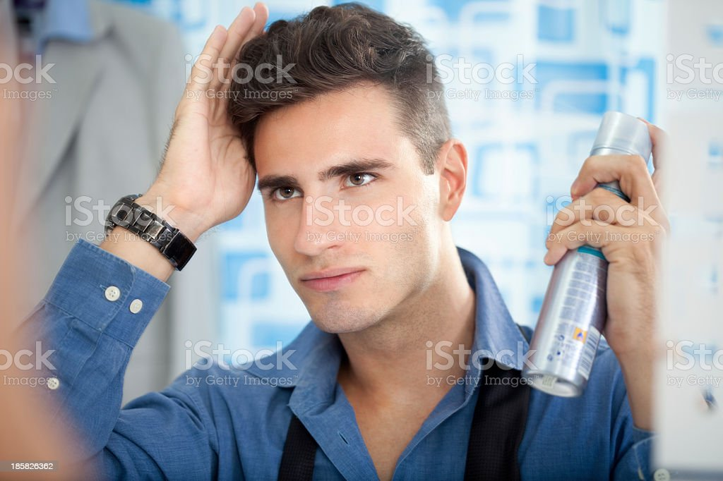 Man styling his hair in the mirror with hairspray stock photo