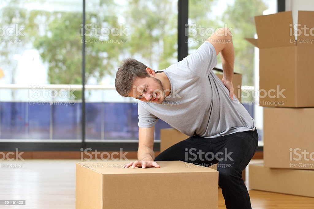 Man suffering back ache moving boxes stock photo