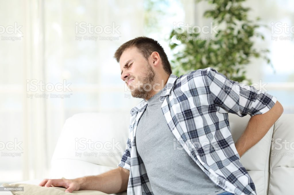 Man suffering back pain at home stock photo