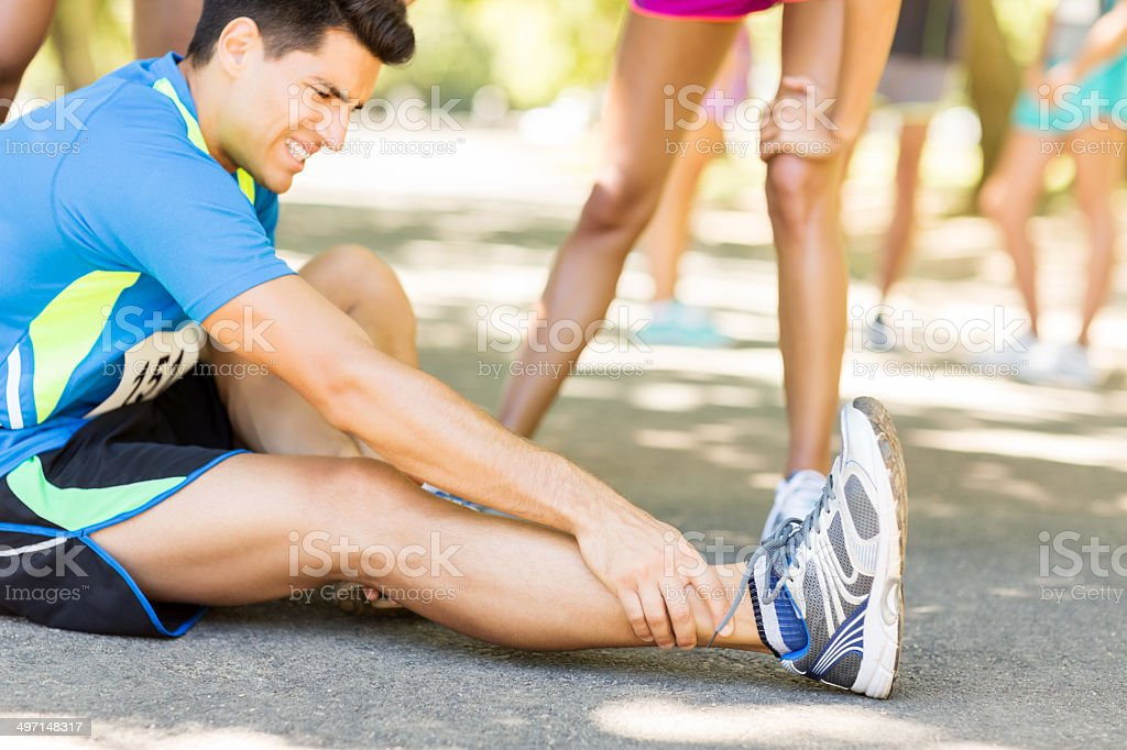 Man Suffering From Ankle Pain On Street During Marathon stock photo