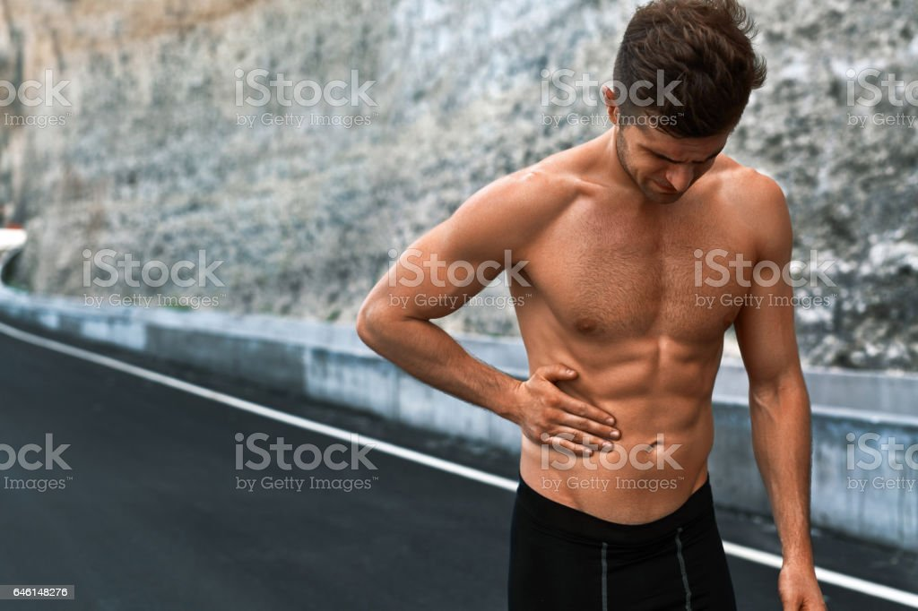 Man Suffering From Stomach Pain After Running Outdoors. Sport Injury stock photo
