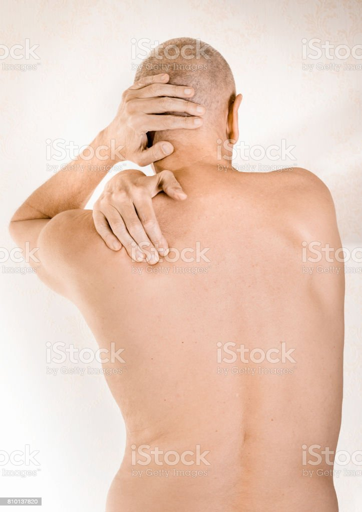 Man suffering of thoracic vertebrae or trapezius muscle pain stock photo