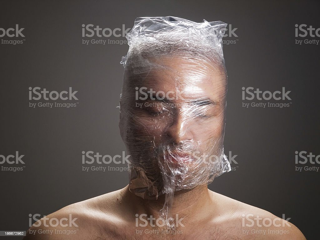 Man suffocating with plastic around his head royalty-free stock photo