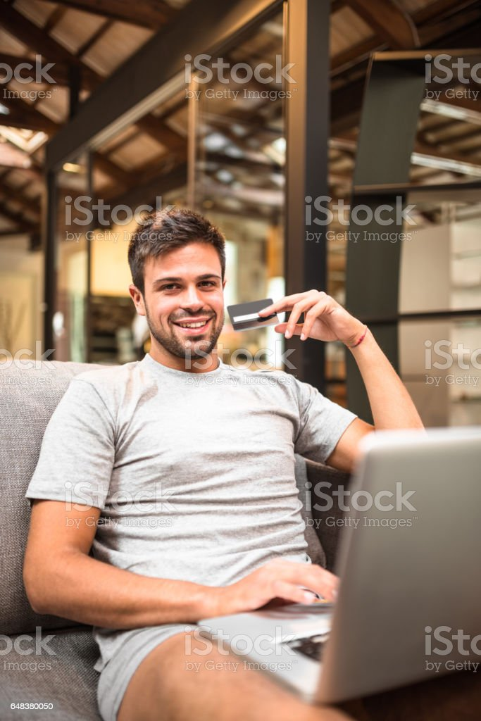 man surfing on the coach and buying on the web stock photo