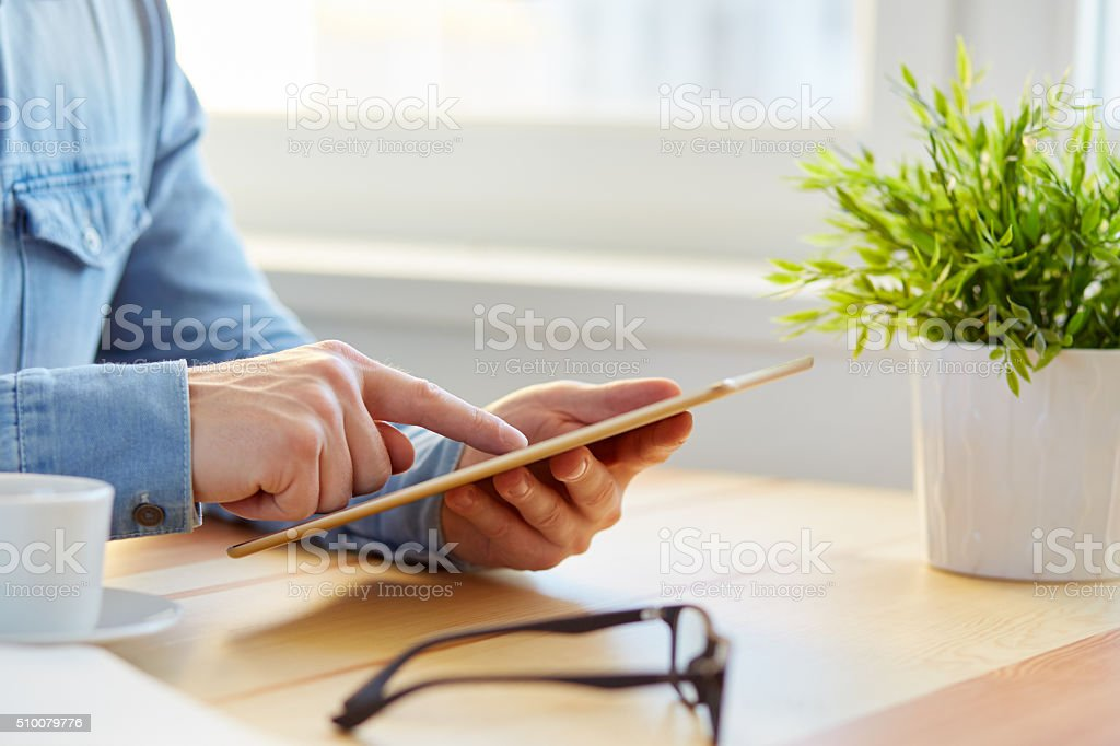 Man surfs the internet with the tablet stock photo