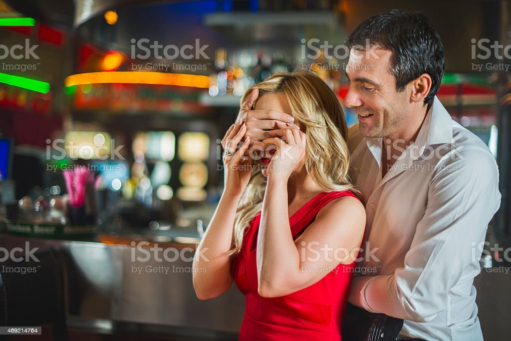 Man surprising a woman in a bar. stock photo