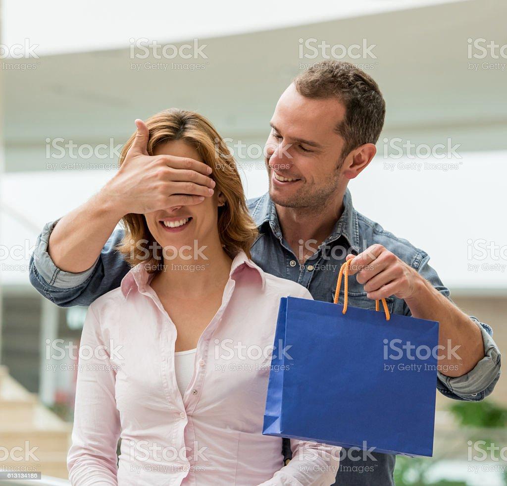 Man surprising woman at the shopping center stock photo