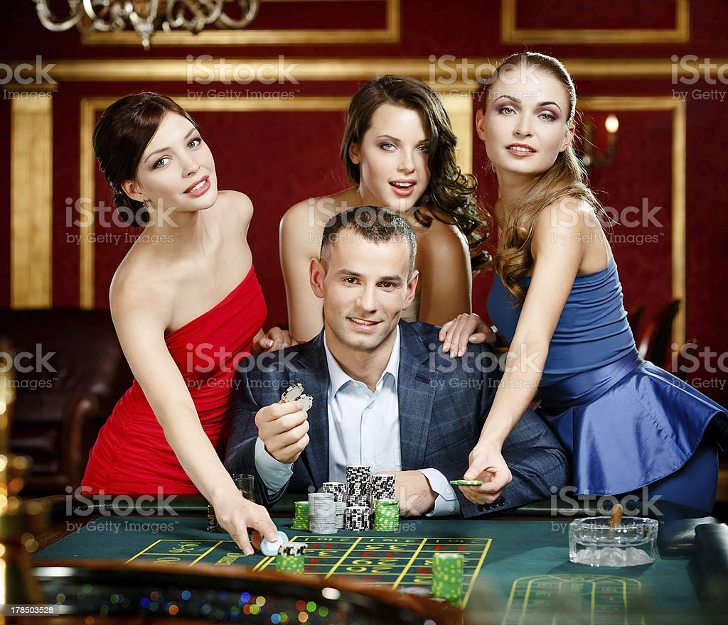 Man surrounded by girls gambles roulette royalty-free stock photo